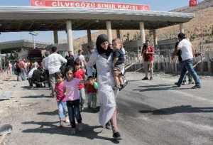 Refugiados sirios cruzan un control migratorio de la frontera Cilvegozu en Reyhanli, Hatay, Turquía, para huir de la violencia y la amenaza de ataques