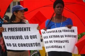 Mujeres sostienen carteles en las afueras del Congreso en apoyo a la legalización del aborto en Santo Domingo, República Dominicana, el martes 16 de diciembre de 2014. La Cámara de Diputados dominicana aprobó la petición del presidente Danilo Medina de despenalizar el aborto en algunos casos, lo que ha dividido a la opinión pública. La propuesta debe ser ratificada por el Senado en los próximos días. (AP Photo/Ezequiel Abiu Lopez)